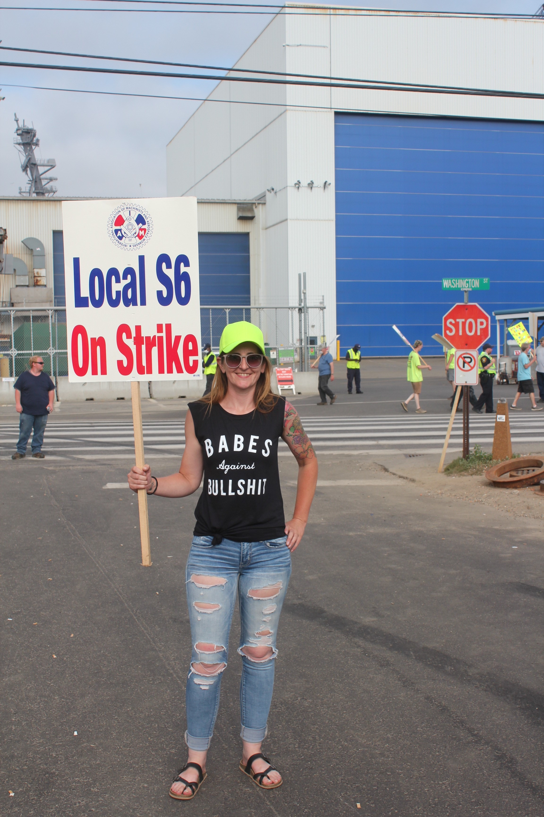Jami holds a 'Local S6 on strike' sign; her shirt says 'Babes against bullshit'