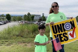 "Woman holding ""UNION YES"" sign and child holding U.S. flag, with VW plant behind"