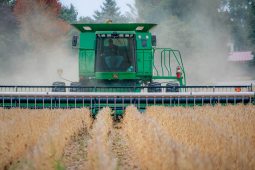 A worker drives a tractor through a field.