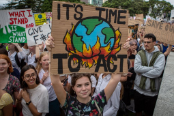 """New Zealand students hold signs with slogans like """"It's Time to Act,"""" with a drawing of the earth being consumed by flames, during a school strike in March 2019."""