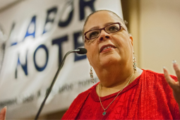 Karen Lewis at the podium in front of Labor Notes banner