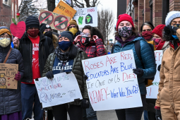 "Crowd in coats and masks. One hand-drawn sign reads ""Roses are red, educators are blue, if one of us dies, Kenney, what will you do?"" Another shows a train and reads ""Choo-choo-choose a safe plan."" Another says ""ventilate, vaccinate, educate."" Another shows an image of a fan with a ""no"" line across it."