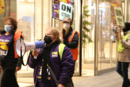 """People in masks and purple SEIU 87 shirts picket in front of a bright window. Central person has a bullhorn. Others carry """"ON STRIKE"""" signs and wear reflective vests."""