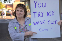 "woman outdoors holds sign: ""You try 10% wage cut Carmel!"""