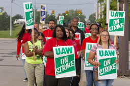 "GM strikers march with ""UAW on strike"" signs. Black and white women in foreground."