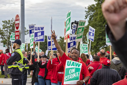 GM workers on a picket line, one work offscreen with arm raised, another centered with sign with arm raised.