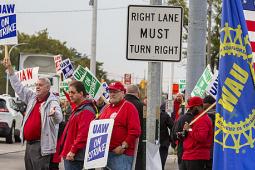 UAW strikers picketing on a street corner.
