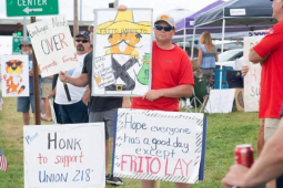 Frito-Lay workers hold signs on the picket line.