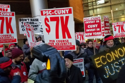 """crowd holding signs including """"PSC-CUNY $7k per course for adjuncts,"""" """"invest in CUNY, invest in New York,"""" and """"ECONOMIC JUSTICE"""" spelled out in lights"""