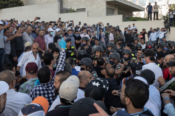 Crowd of teachers and supporters protesting in Amman in front of building, some with raised arms, on July 29 2020
