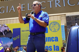 Man in blue shirt with right arm raised and left arm holding microphone addressing crowd, Fuera LUMA flag visible in foreground, building of Puerto Rico Electric Power Authority (PREPA)