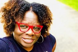 Close-up selfie of Petal Robertson, a Black woman with red glasses, smiling into the camera, outdoors