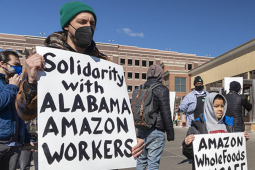 Adult and boy with signs in front of Whole Foods supporting Alabama Amazon workers attempting to unionize.