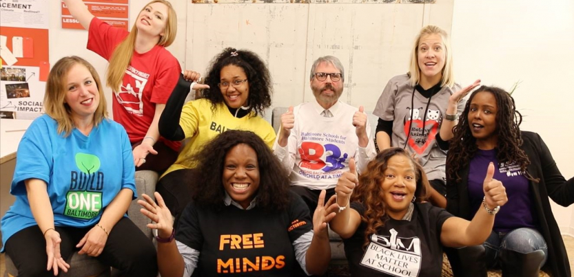 "Eight teacher leaders from the Unions We Deserve slate pose together, smiling and giving thumbs-up. T-shirt slogans include ""flree minds,"" ""Black lives matter at school,"" ""Baltimore schools for Baltimore students,"" and ""build one Baltimore"""
