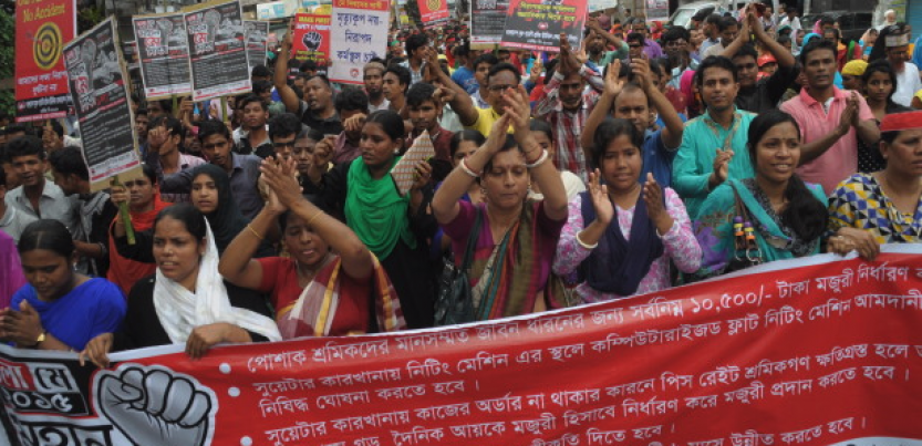 Bangladeshi workers rally behind a banner