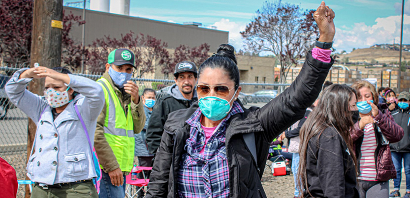 Woman with fist up amidst farmworkers on strike