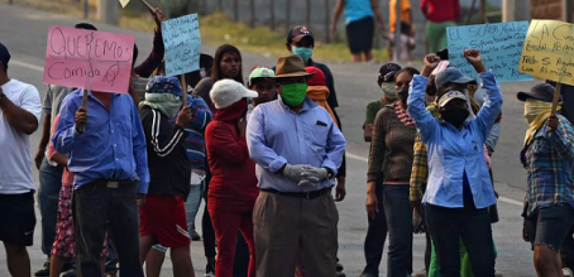 Group of protesters in Honduras assembled in the street with signs