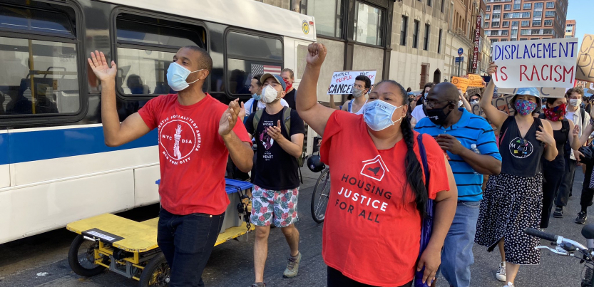 Marchers wearing masks walk through the streets of New York City, with Jabari Brisport and Marcela Mitaynes in the front.