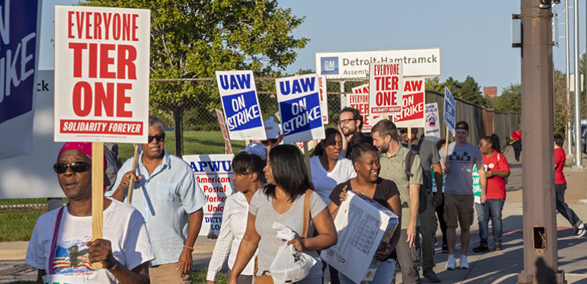 Group of UAW strkers picketing with signs against tiered wages.