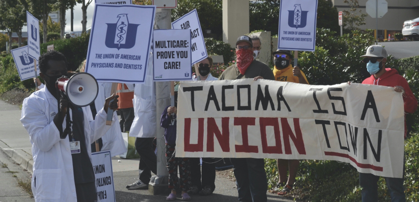 """Urgent care doctors and staff in white coats picket alongside a sign held by union supporters that reads """"Tacoma Is a Union Town."""""""
