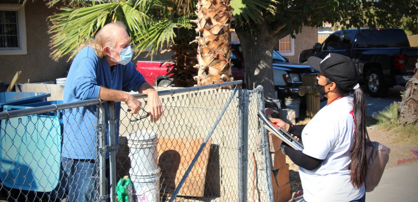 A Latina canvasser wearing a mask and holding a clipboard speaks to an older man leaning on his gate about the election