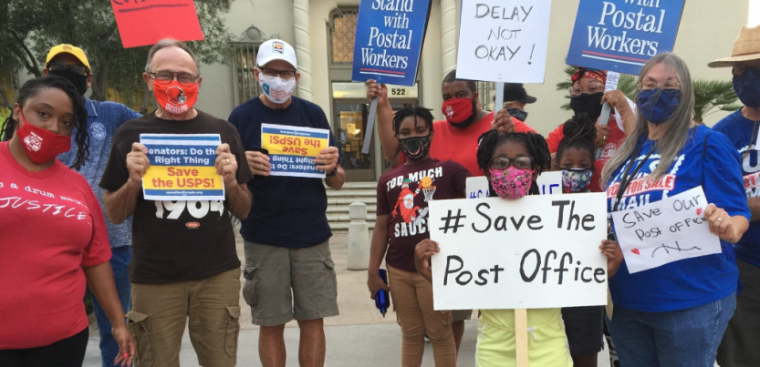 """Masked people (Black and white, men and women) holding signs. Most prominent is a handwritten sign: """"#Save the Post Office."""" Preprinted signs say """"Stand with Postal Workers"""" and """"Senators, do the right thing! Save USPS"""""""