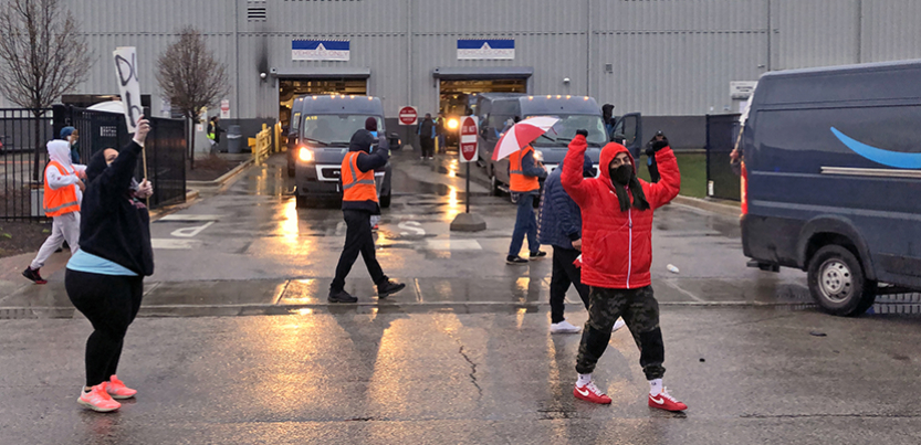 Amazon workers picketing in the parking lot of their warehouse.