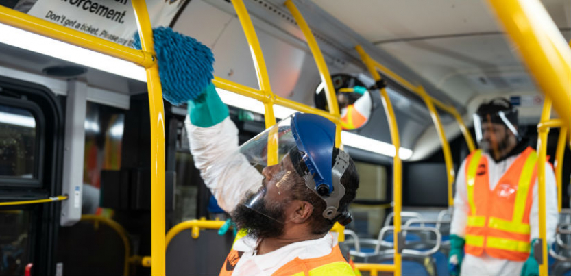 A worker cleaning a yellow pole with disinfectant on a NYC bus with another worker looking on. the workers are wearing orange safety vests, helmets, and transparent visors.