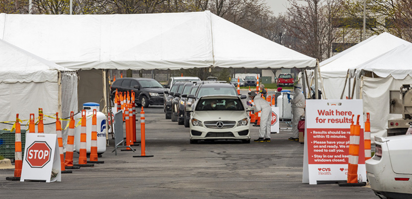 A line of cars coming through a coronavirus testing site in a parking lot. Site has tents.