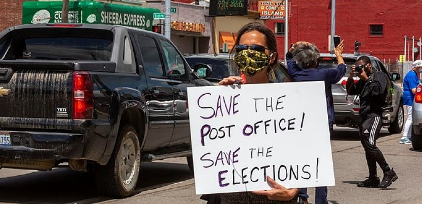 """A masked protester holds a sign: """"Save the Post Office! Save the Elections!"""" Behind the person, traffic and a """"Coney Island"""" (diner) across the street"""