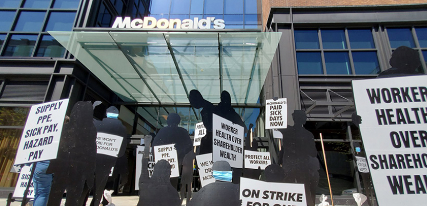 black silhouette cutouts representing workers on trike in front of mcdonald's