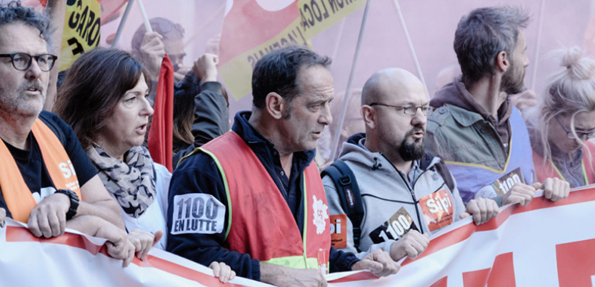 Characters from the film hold up a banner.