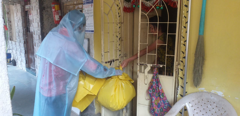 Dalit sanitation worker in a PPE suit accepting trash in yellow bags by hand from the home of a coronavirus patient
