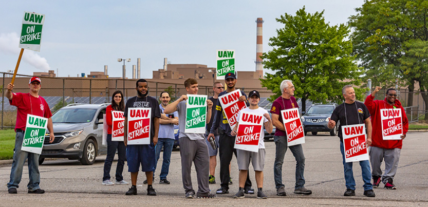 GM strikers picketing on the road holding signs.