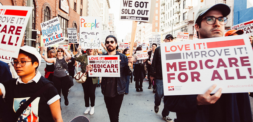Protest in 2017 with signs that support Medicare for All, people marching in the street