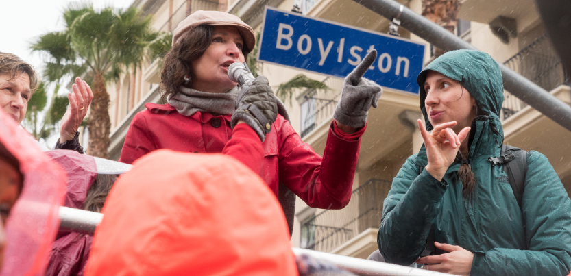 "A woman speaks at a strike rally while another woman interprets in sign language. Behind them is a palm tree, an apartment buidling or hotel, and a street sign ""Boylston"""