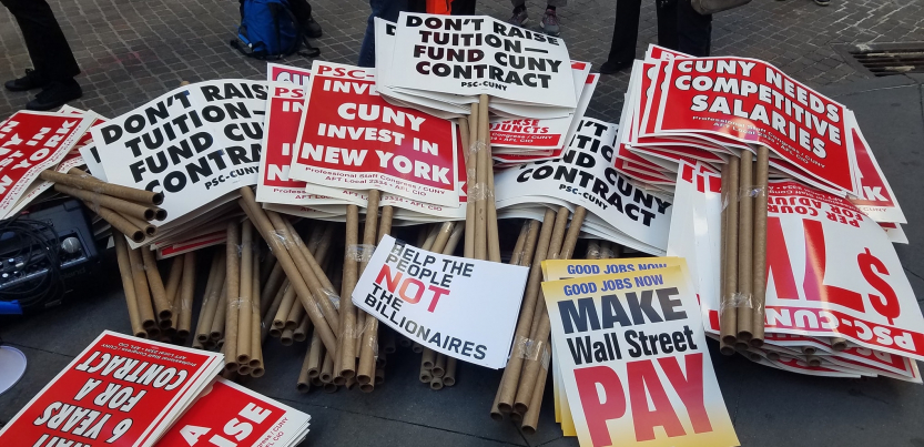 "stack of picket signs including ""don't raise tuition, fund CUNY contract,"" ""good jobs now, make Wall Street pay,"" ""CUNY invest in New York,"" ""help the people, not the billionaires,"" and ""CUNY needs competitive salaries"""