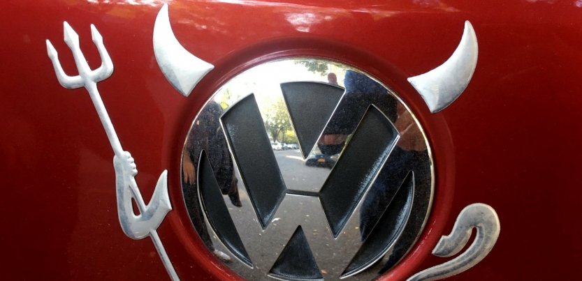 Devil horns, pitchfork, and tail have been added to the VW logo on a car
