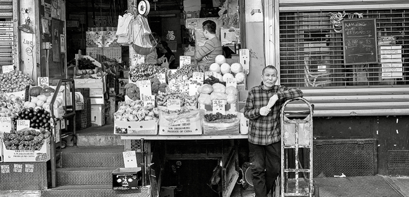 Produce seller with his sidewalk stand in Chinatown, New York, in front of store