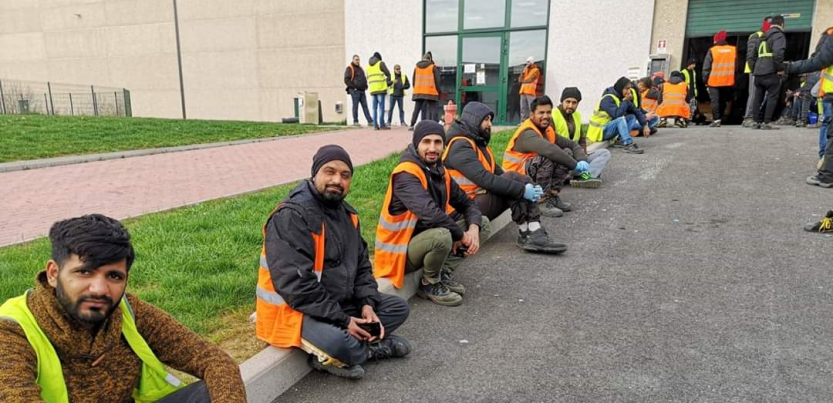 Workers in Italy sitting outside a warehouse on strike in orange vests.