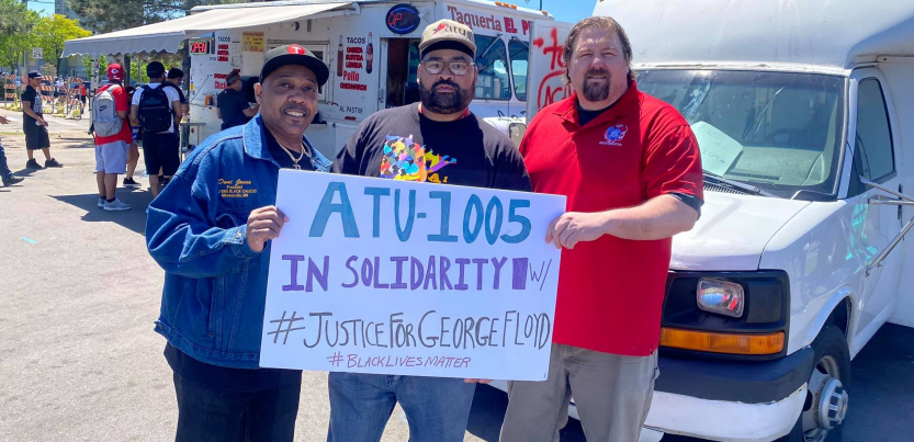"Three men (two Black, one white) hold a sign: ""ATU-1005 in solidarity w/ #JusticeForGeorgeFloyd #BlackLivesMatter."" Taco truck in background."