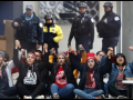 Teachers seated on sidewalk with joined hands raised; police standing behind them