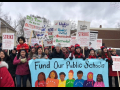 """Strikers carry a banner """"Fund Our Public Schools"""" with a rainbow of faces. Picket signs say """"Strike"""" and """"It's Time to Use Our Outside Voice."""" One kid is carried on an adult's shoulders."""