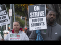 """A white man and a Black man hold signs: """"On Strike for Our Students; UTLA"""""""