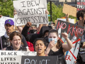 """Marchers with signs including """"IBEW Against Oppression"""" and """"No KKKops"""""""