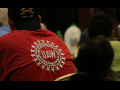 Back of man in red UAW shirt seated at event.