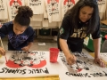 """Two people painting signs that say """"public schools are the heart of the community"""""""