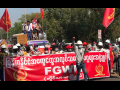 Dozens of workers march behind a red banner in Myanmar. Some carry red flags.