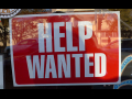Help Wanted sign - background red, text white, in window of store
