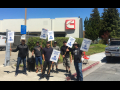 Members of Machinists Local 1546 stand in front of their workplace holding picket signs.